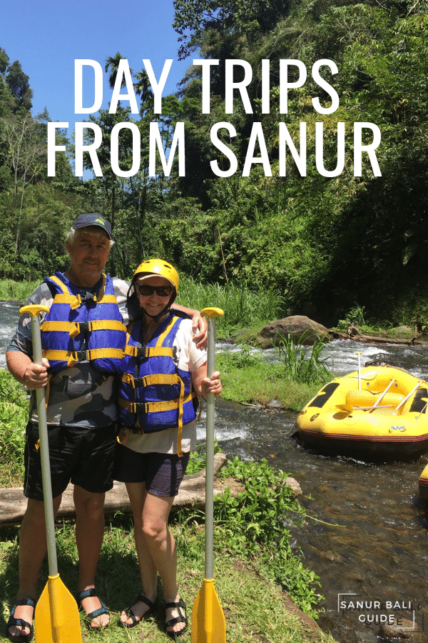A couple standing with Oars with a raft nearby from White Water Rafting in Bali